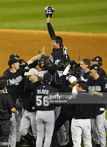 The Florida Marlins hoist up pitcher Josh Beckett the 2003 World Series MVP after defeating the New York Yankees 2-0 in game six of the Major League...