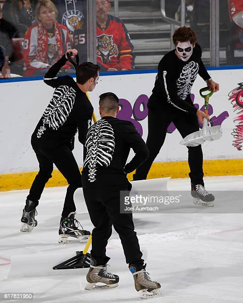 The Florida Panthers ice crew in halloween costumes clean the ice during a break in action against the Colorado Avalanche at the BBT Center on...