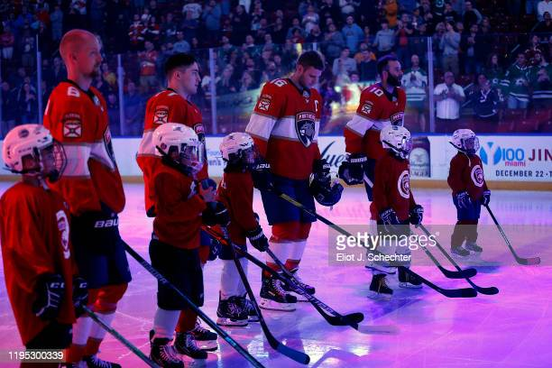 The Florida Panthers stand on the ice for the national anthem with guest skaters prior to the start of the game against the Dallas Stars at the BB&T...