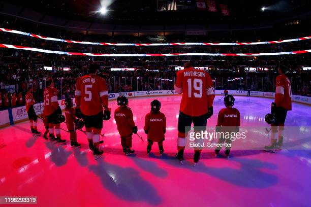 The Florida Panthers stand on the ice with guest skaters for the national anthem prior to the start of the game against the Arizona Coyotes at the...