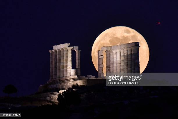 The flower full moon rises behind the 444-440 BC Temple of Poseidon at Cape Sounion, some 70 km south of Athens on May 26, 2021. AFP/Louisa Gouliamaki