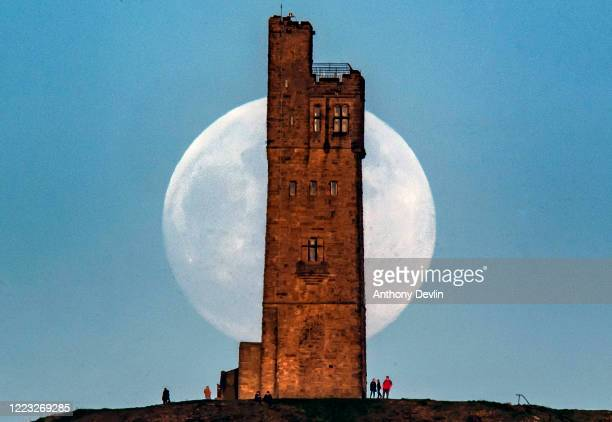 The Flower Moon is seen 99% full as it rises behind Victoria Tower on Castle Hill on May 06 2020 in Huddersfield England The Flower Moon is this...