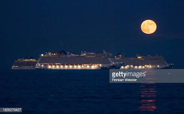 The Flower Moon rises over the cruise ships Norwegian Escape and Norwegian Bliss in the bay on May 26, 2021 in Weymouth, United Kingdom. May's full...