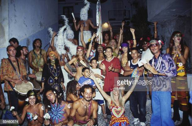 The Flower Power Performers from Pacha and the Monsters from Privilege pose with street kids at the Flower Power Parade in Ibiza Town 2000