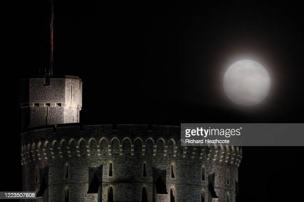 The Flower Super Moon rises over Windsor Castle on May 07 2020 in Windsor United Kingdom A supermoon occurs when the moon reaches its closest...