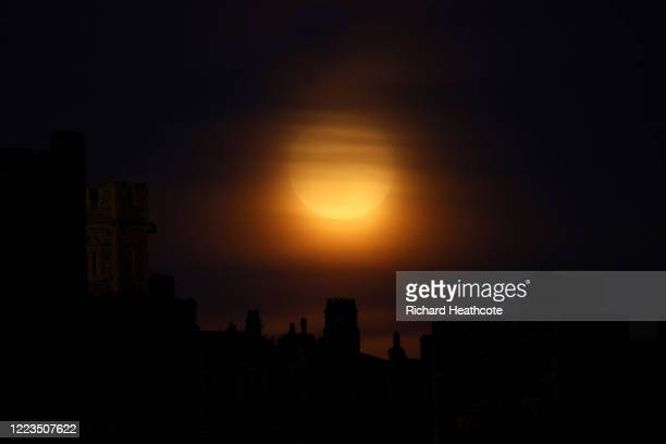 The Flower Super Moon rises over Windsor on May 07 2020 in Windsor United Kingdom A supermoon occurs when the moon reaches its closest position to...