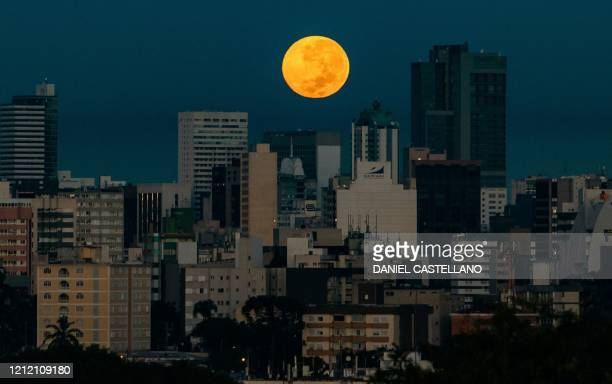 The Flower Supermoon rises over Curitiba, Brazil on May 7, 2020. - The supermoon is visible as the full moon coincides with the satellite in its...
