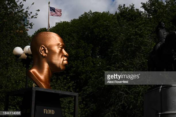 """The """"Floyd"""" sculpture is displayed near a waving American flag after a press conference for Confront Art's First Exhibition launch SEEINJUSTICEin..."""