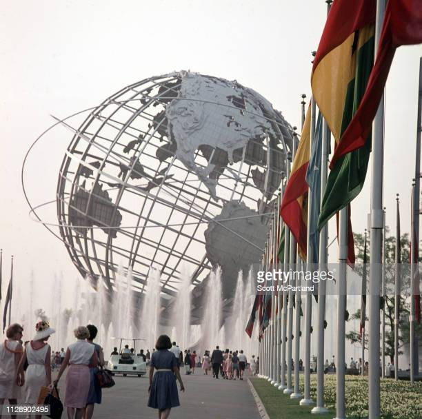 The Flushing Meadows Unisphere looms over visitors on a flaglined walkway during the World's Fair in Queens New York New York June 1965