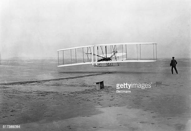 The Flyer takes off from Kill Devil Hill with Orville Wright at the controls while his brother Wilbur looks on on December 17 1903