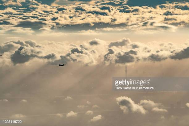 The flying airplane and Tokyo Sky Tree in the sunset clouds sunset time aerial view from airplane