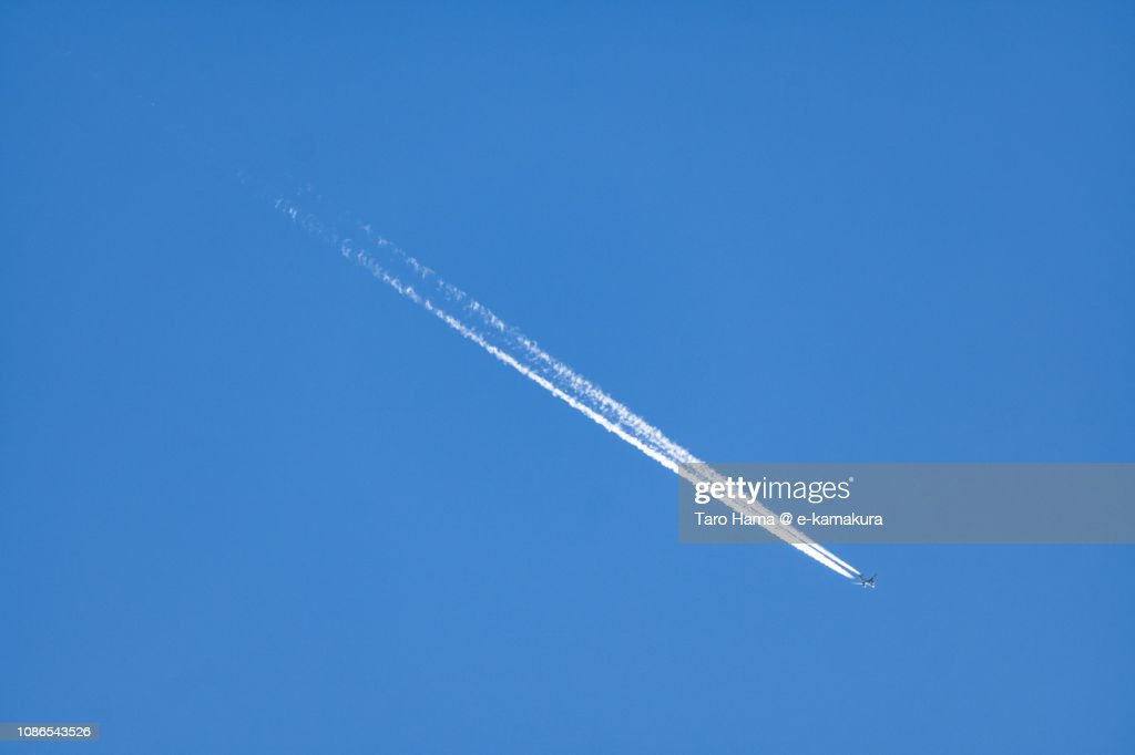 The flying airplane and vapor trail in the blue sky in Japan : Stock Photo