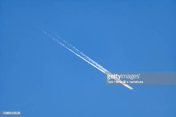 The flying airplane and vapor trail in the blue sky in Japan
