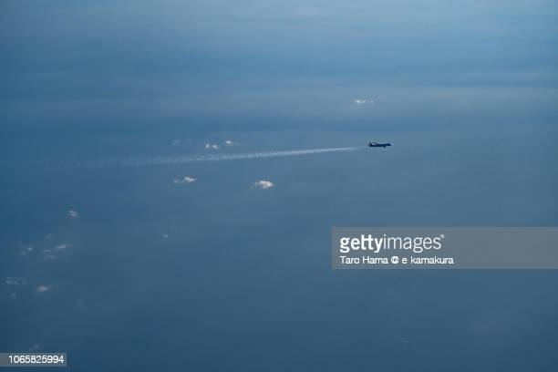 The flying airplane on Pacific Ocean in Japan daytime aerial view from airplane