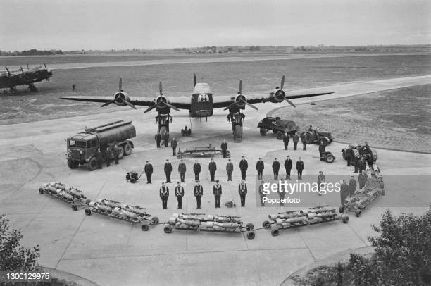 The Flying crew and ground crew stand together with associated bomb train and fuel tanker on a turning apron in front of a Royal Air Force Short...