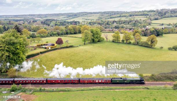 """The Flying Scotsman train passes the village of Shere better know as the set for the Christmas film """"The Holiday"""" on May 20, 2021 in Shere ,England."""