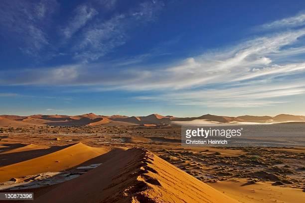 The fog from the ocean (atlantic) between the red dunes. Sossusvlei, Namib Desert, Namibia