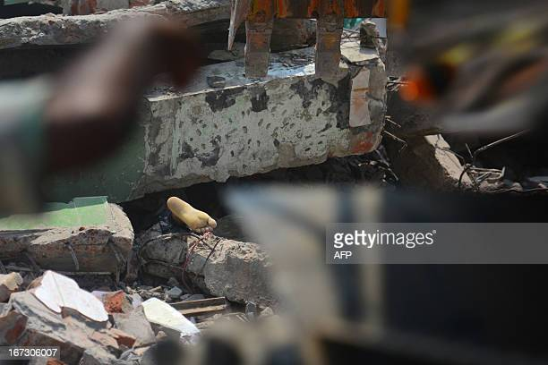 The foot of a victim is seen amid the rubble after an eight-storey building collapsed in Savar, on the outskirts of Dhaka, on April 24, 2013. At...