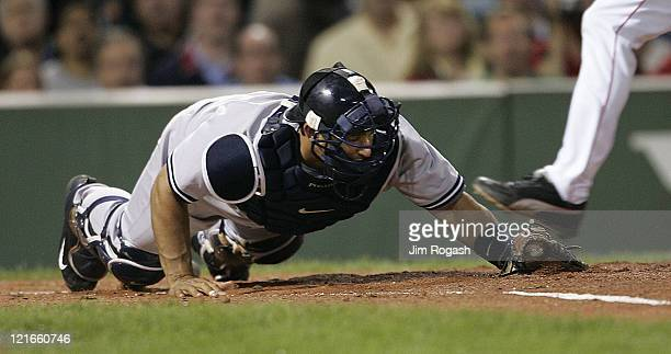 The foot of Boston Red Sox's Johnny Damon does not beat New York Yankees catcher Jorge Posada who tags home for the force out at Fenway Park in...