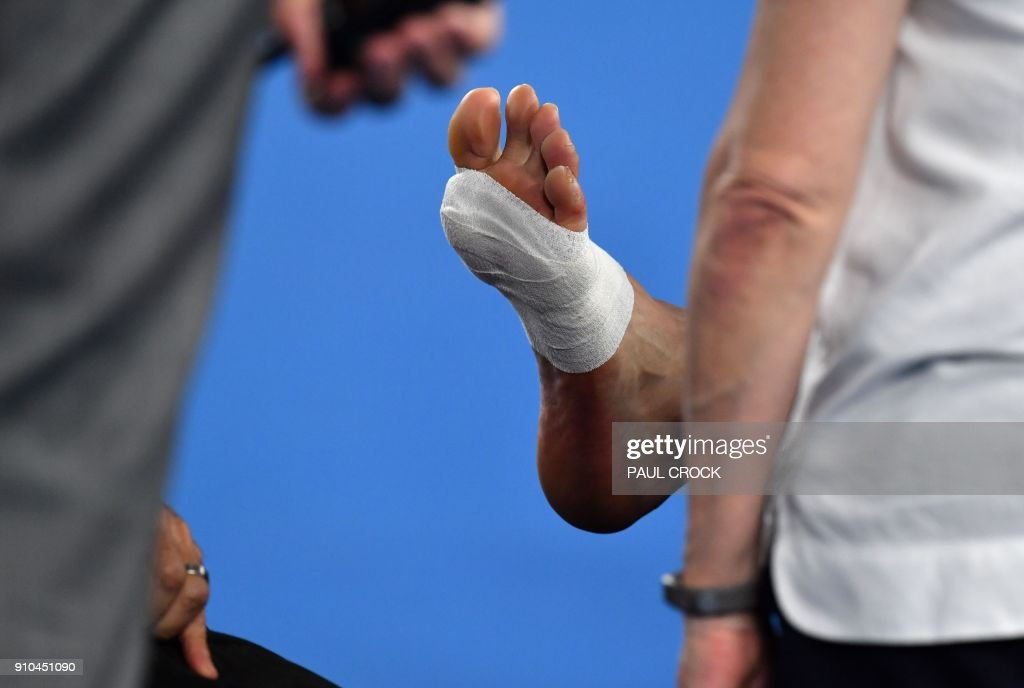 The foot of South Korea's Chung Hyeon is seen as he receives medical attention against Switzerland's Roger Federer during their men's singles semi-finals match on day 12 of the Australian Open tennis tournament in Melbourne on January 26, 2018. / AFP PHOTO / Paul Crock / -- IMAGE