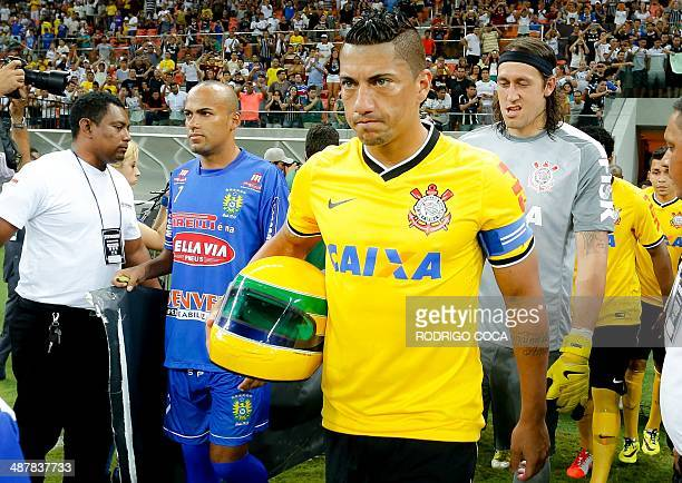 The football player Ralf of Corinthians football club holds a replica of the helmet worn by Brazilian's F1 driver Ayrton Senna before the start of...