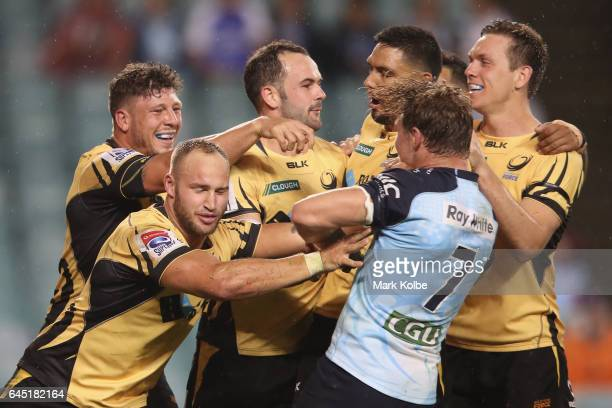 The Force players exchange heated words with Michael Hooper of the Waratahs as they celebrate a try scored by Jono Lance during the round one Super...