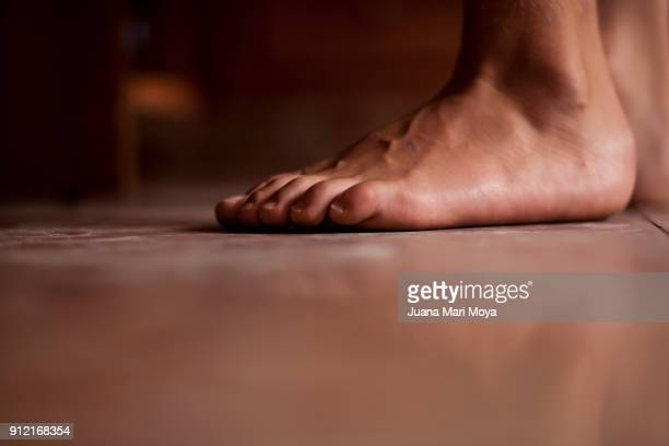 The foreground of bare feet. To the Ground