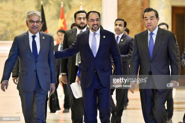 The foreign ministers of China Afghanistan and Pakistan Wang Yi Salahuddin Rabbani and Khawaja Asif walk to a press conference room at the Diaoyutai...
