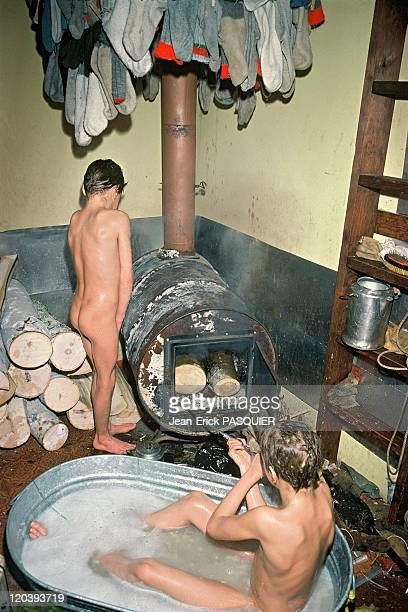 The forest people in Alaska United States Children from the Stultz family taking their bath The woodburning stove is used to melt and heat snow used...