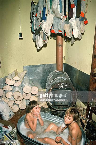 The forest people in Alaska United States The Stultz family children taking their bath The woodburning stove is used to melt and heat snow used as...