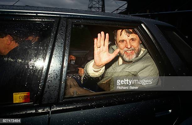 The former Beirut hostage Terry Waite waves from a car driven away after landing back at RAF Lyneham UK Looking exhausted with red eyes a drawn...