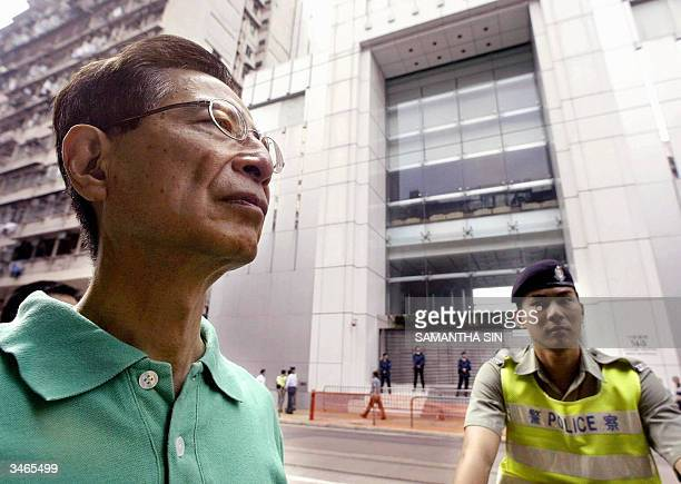 The former chairman of the Democratic Party Martin Lee is watched by a policeman during a protest outside the Government Liason Office in the Western...