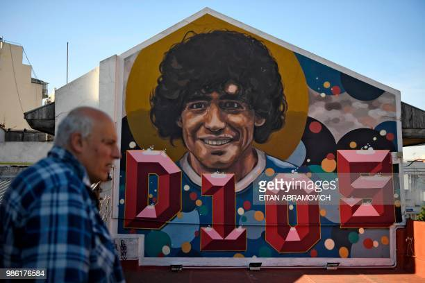 The former director of Argentinos Juniors sports club and owner of the 'Casa de Dios' museum, Alberto Perez, walks past a mural of Argentine football...