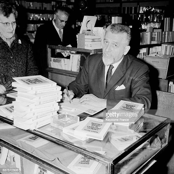 The former minister Robert Buron dedicates his book 'Political books of the Algerian war' in a bookseller of the Clichy square on 8 April 1965 in...