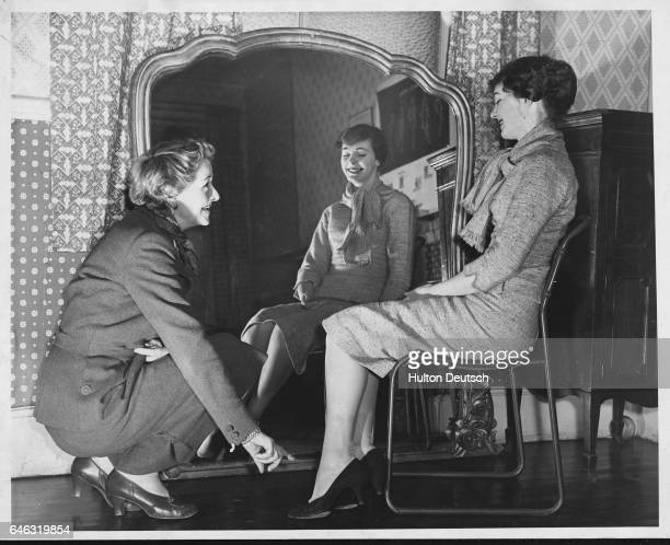 The former model Yvonne McMahon demonstrates how to sit correctly to Elena Houston a dress design student from Kingston Art School 1958