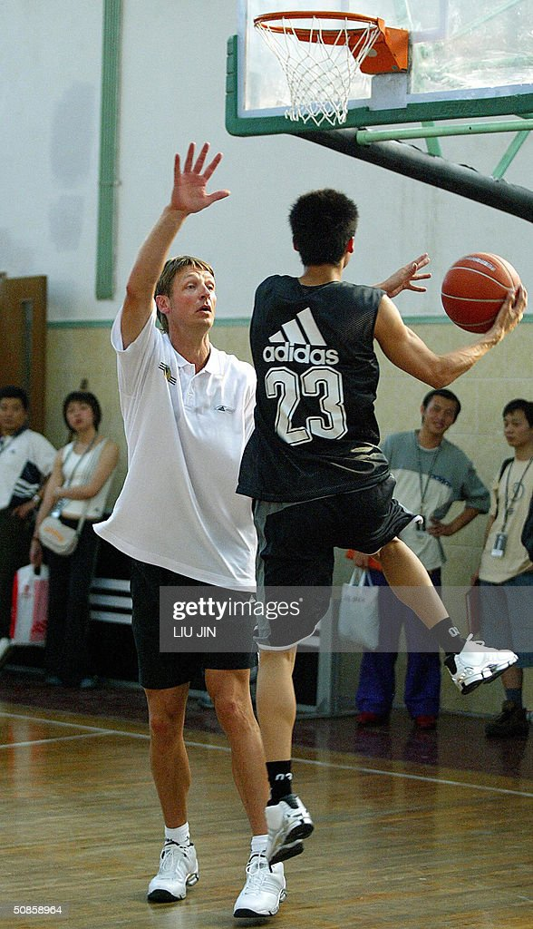The former NBA star Detlef Schrempf (L) trains a young player in a training session of the Adidas Basketball Superstar Camp in Shanghai, 20 May 2004. The camp features NBA players and professional coaches from the US, Europe and China to develop future generations of Basketball superstars. Fifty elite youth basketball players from China, Hong Kong, Australia, Philippines, Korea, Chinese Taipei, Singapore participate the four-day training event. AFP PHOTO/LIU Jin