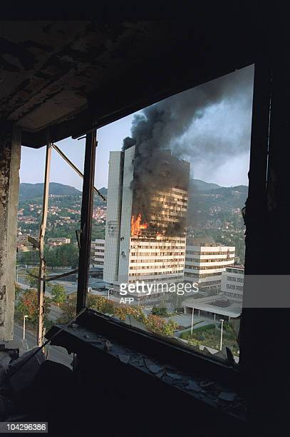 The former Parliament building is seen burning from a destoyed upper floor of the Holiday Inn Hotel in Sarajevo after being hit by Serbian tank fire...