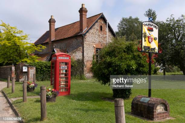 The former phone kiosk that now serves the local village community with a bring and borrow book library service, on a viillage green in rural...