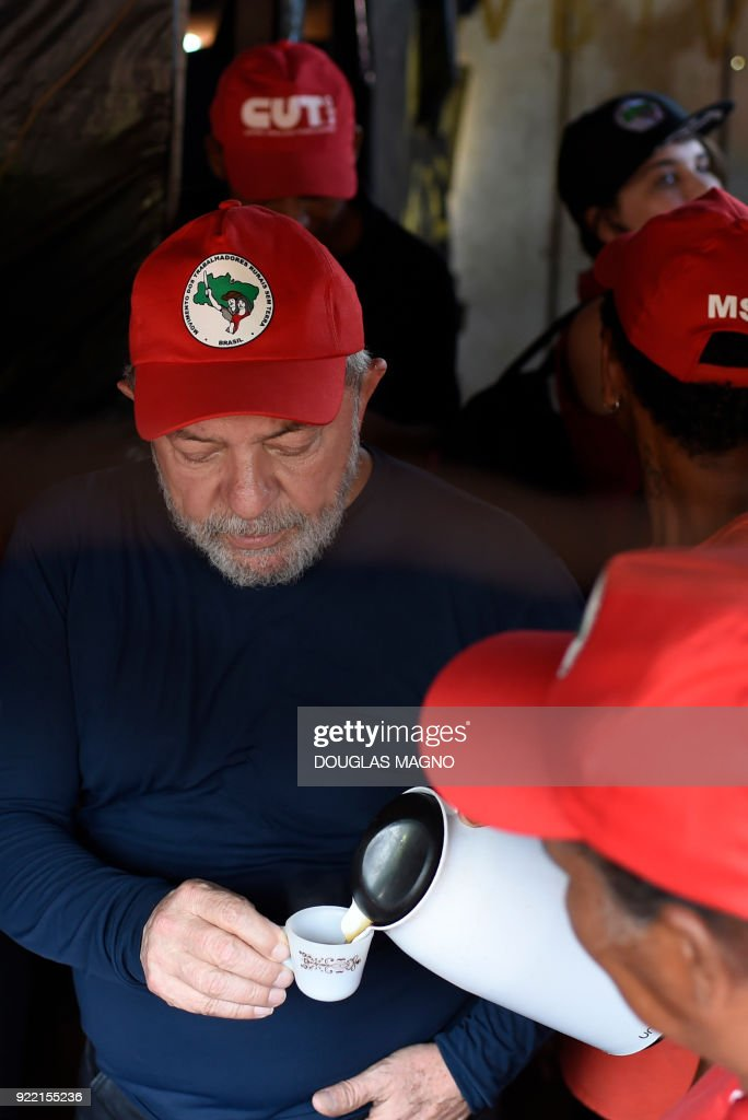 The former president of Brazil, Luiz Inacio Lula da Silva(C)takes coffee during a visit at a camp of the Landless Workers Movement (MST)on the municipality of Itatiaiucu, metropolitan region of Belo Horizonte in the state of Minas Gerais on February 21, 2018. Brazil's former leftist president Luiz Inacio Lula da Silva made yet another appeal against a 12 year prison sentence for corruption that could knock him out of an attempted comeback election. /