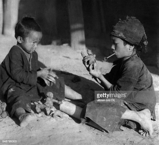The former state Siam Three small Siam boys sittig on the ground making some toys of clay by themselves ca 1937 Photographer Hugo Adolf Bernatzik...