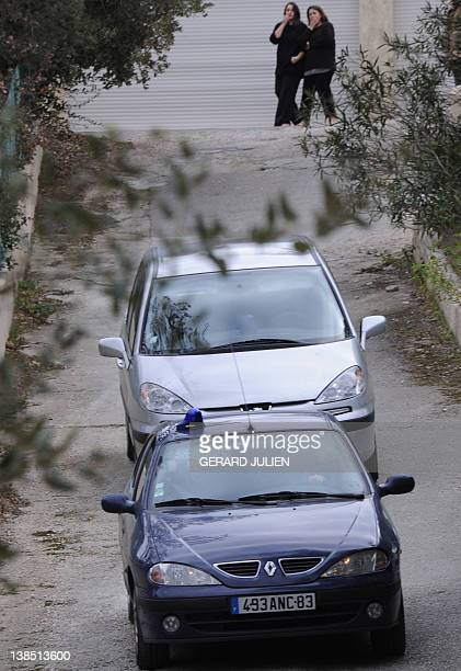 The former wife and the daughter of Jean Claude Mas watch from JeanClaude Mas leaves his companion's home in a gendarmerie car on January 26 2012 in...