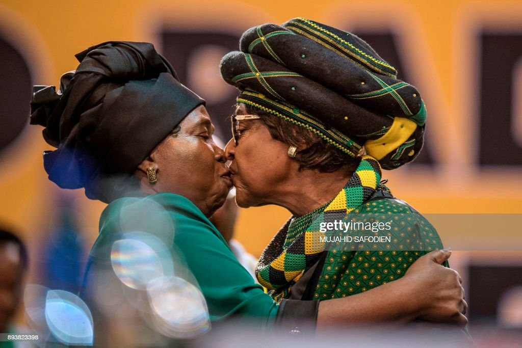 TOPSHOT - The former wife of the late South African President Nelson Mandela, anti-apartheid campaigner Winnie Mandela (R), and the candidate for the African National Congress presidency and ex-wife of the incumbent South African president, Nkosazana Dlamini-Zuma greet each other as they attend the 54th ANC National Conference at the NASREC Expo Centre in Johannesburg on December 16, 2017. Thousands of delegates from South Africa's ANC party gathered on December 16, 2017 for a five-day meeting to elect their new leader in a divisive race seen as a pivotal moment in the country's post-apartheid history. he winner will be well placed to be the next president, but the ANC has lost much popularity since Nelson Mandela led it to power in the euphoric 1994 election that marked the end of white-minority rule. SAFODIEN