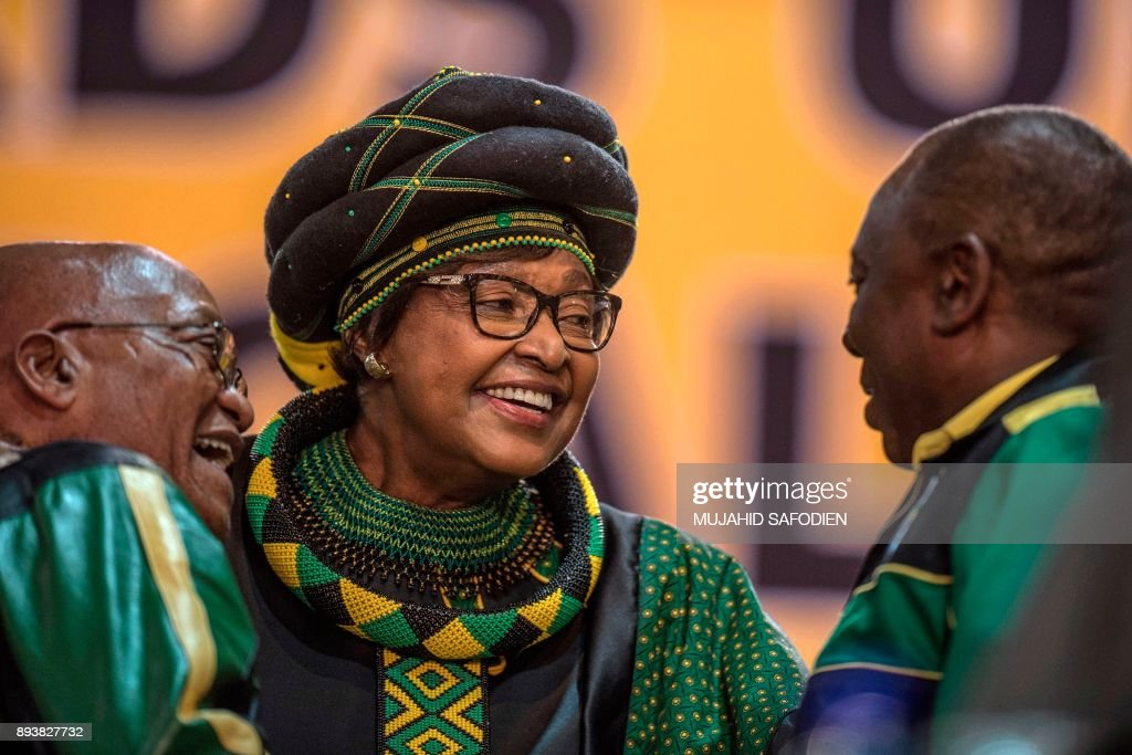 The former wife of the late South African President Nelson Mandela, anti-apartheid campaigner Winnie Mandela (C), hugs South African President Jacob Zuma (L) and Deputy President Cyril Ramaphosa as they attend the 54th ANC National Conference at the NASREC Expo Centre in Johannesburg on December 16, 2017. Thousands of delegates from South Africa's ANC party gathered on December 16, 2017 for a five-day meeting to elect their new leader in a divisive race seen as a pivotal moment in the country's post-apartheid history. he winner will be well placed to be the next president, but the ANC has lost much popularity since Nelson Mandela led it to power in the euphoric 1994 election that marked the end of white-minority rule. SAFODIEN