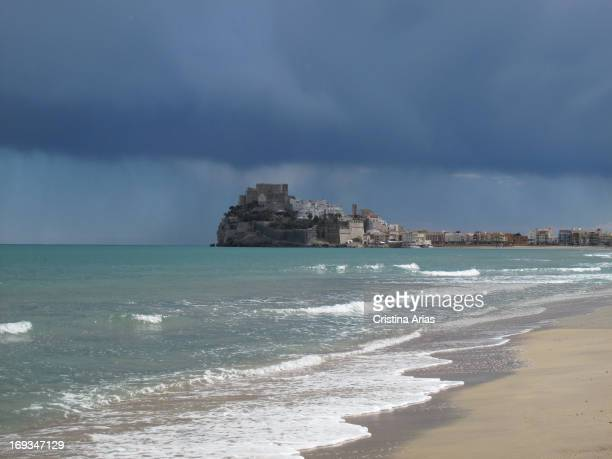 The fortified citadel of Peniscola with the Papa Luna Castle at the top, seen from the North Beach on a day of storm, Castellon, Valencian Comunity,...