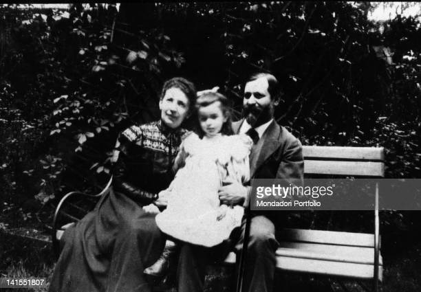 The founder of psychoanalysis Sigmund Freud sitting on a bench next to wife Martha Bernays and with daughter Anna on his lap. Austria, 1900s