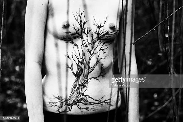 the fountain,  painted tree on a woman's body - brustwarzen piercing stock-fotos und bilder