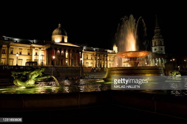 The fountains in Trafalgar Square are illuminated in yellow light as part of the National Day of Reflection on the anniversary of the first national...