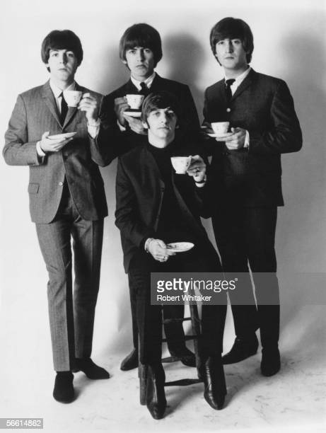 The four members of the Beatles posing with cups of tea Paul McCartney George Harrison John Lennon and Ringo Starr October 1965