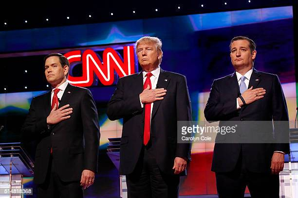 The four remaining Republican primary candidates Marco Rubio Donald Trump Ted Cruz and John Kasich listen to the National Anthem at the beginning of...