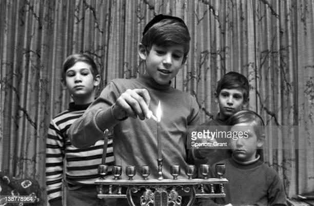 The four sons of a Jewish family light a menorah during Hanukkah, Brookline, Massachusetts, 1971.